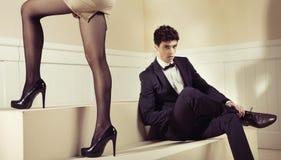 Heureux homme regardant les jambes bien faites de son amie Images stock