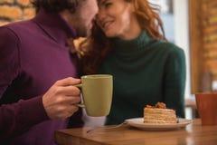 Heureux jeune homme et femme buvant la boisson chaude en café Photos libres de droits