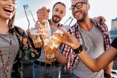 Heureux jeunes amis faisant tinter des verres d'alcool Photographie stock