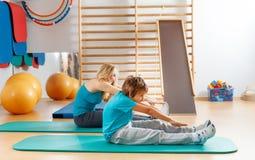 Heureux, les sports famille, la mère et le fils exécutez les exercices gymnastiques photos libres de droits