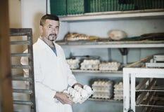 Heureux oeufs de poule blancs de fonctionnement et d'emballage d'homme Photographie stock