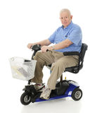 Heureux supérieur avec son scooter Photo stock