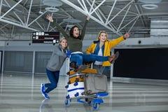 Heureux touristes roulant sur le chariot à bagage Images stock