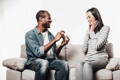 Heureux type proposant son amie étonnée devenant une épouse Image stock