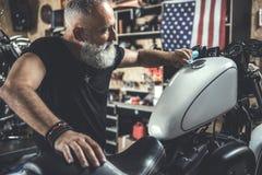 Heureux vieil homme près de motocyclette Photographie stock