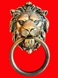 Heurtoir de porte en bronze de lion sur le fond rouge Photos libres de droits