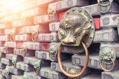 Heurtoir de porte principal de lions antiques de fer situ? sur un mur de briques La Chine photo stock