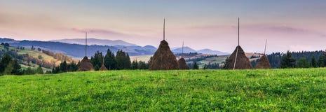 Heuschober in einem Tal am Gebirgshintergrund Lizenzfreies Stockbild