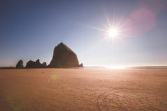 Heuschober-Felsen und der Sun im Kanonen-Strand, Oregon Lizenzfreies Stockbild