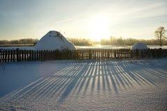 Heuschober, Zaun und Schnee im Dorf Lizenzfreies Stockfoto