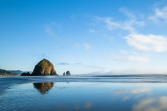 Heuschoberfelsen reflektierte sich im nassen Sand des Ozeanstrandes Stockfoto