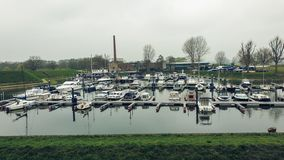 Heusden, Netherlands - 6 April 2019: Boats docked in the harbor, waiting for a nice day royalty free stock image