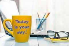 HEUTIGER TAG IST IHR TAGEStext auf gelbem Becher mit Morgentee oder -kaffee am Geschäftslokalhintergrund Motivkonzept Lizenzfreie Stockfotografie