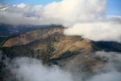 Heuvel die tussen de wolken wordt gezien stock foto