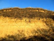 Heuvel met droog die gras door de het plaatsen zon wordt aangestoken Stock Afbeelding