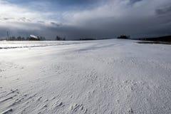 Heuvel met wind-opvlammende sneeuw en zonsondergang Stock Afbeeldingen