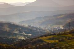 Heuvelhellingen rond klein dorp Het landschap van de lente Ochtendlandschap stock foto's