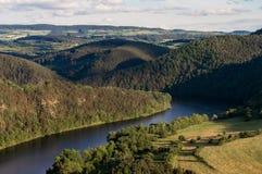Heuvelig landschap met rivier stock foto