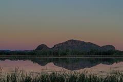 Heuvels bij zonsondergang worden weerspiegeld die Royalty-vrije Stock Afbeelding