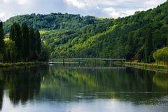 Heuvels en brug met bezinning in rivier Stock Foto