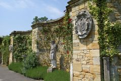 Hever castle Italian garden, Kent, England. Decorative wall with statue and coat of arms in a British castle Royalty Free Stock Photos