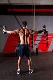 Hex dumbbells man workout rear view at gym Royalty Free Stock Images