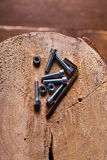 Hex head screw, nut and hexagon key on a wood background Stock Photography