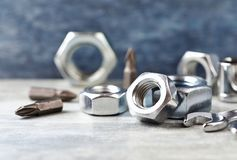 Hex nuts and bits for a screwdriveron wooden background. Close up. Copy space royalty free stock image
