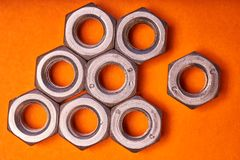Hex nuts on orange background. Bolted connection elements.  royalty free stock photos