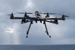 Hexacopter-Brummen, das über den Ozean fliegt Stockfoto
