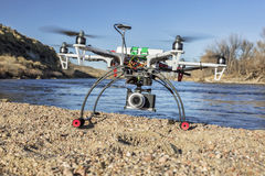 Hexacopter drone with camera landing. WILDCAT, CO, USA, March 9, 2015: DJI F550 Flame Wheel hexacopter drone landing with a camera on river shore stock images
