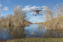 Hexacopter drone flying over lake Royalty Free Stock Images