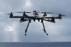Hexacopter drone flying over the ocean. Close up view of a hexacopter drone in midair flying over the ocean against a backdrop of stormy grey clouds and a rain stock photo