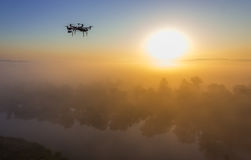 Hexacopter drone over foggy sunrise on river. Landscape Royalty Free Stock Photo