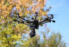 Hexacopter with Surveillance Camera. A drone, hexacopter, with a surveillance camera hovering in the air stock images