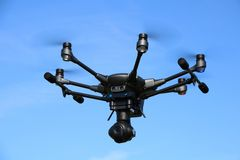 Hexacopter with Surveillance Camera. A drone, hexacopter, with a surveillance camera hovering in a blue sky royalty free stock image
