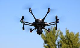 Hexacopter with Surveillance Camera. A drone, hexacopter, with a surveillance camera hovering in a blue sky stock images