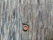 Hexagonal bolt on plank. Rust hexagonal bolt on old plank brown color stock photos