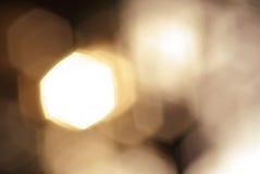 Hexagonal golden light spot transitions - blurred background Stock Images