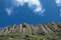 Hexagonal Rock Columns, Kildonan Cliffs, Eigg. Bright blue sky, puff of cloud, looking up rock formations at Kildondan cliffs, Eigg, Scotland Royalty Free Stock Image