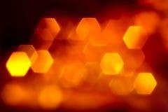 Hexagone orange flat lights. Bright orange flat hexagone lights bokeh on black background royalty free stock image