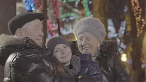 Excited happy old married couple grandparent hug grandchild boy grandson in christmas light festive illumination evening stock footage