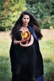 Hexe, die eine Feuerkugel hält lizenzfreies stockbild