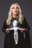 Hexe, die eine Wodupuppe hält Kostüm für Halloween-Partei Blonde Hexe Lizenzfreie Stockbilder