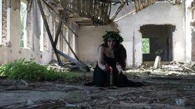 Hexe, die maleficent Geist mit Beschwörung und Kerzen in einer verlassenen ruinierten Villa beschwört und hervorruft stock video footage