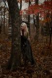 Hexe in einem langen schwarzen Kleid stockfotografie