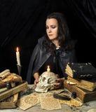 Hexe mit dem Schädel und den Büchern Stockfoto