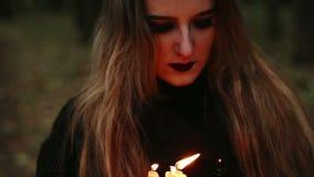 Hexe mit einem Buch und Kerzen im Wald stock footage