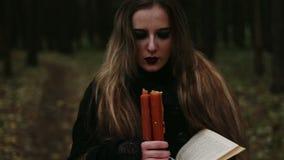 Hexe mit einem Buch und Kerzen im Wald stock video