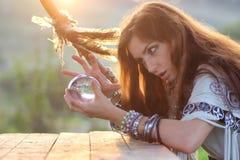 Hexe mit Glaskugel bei Sonnenuntergang Stockbilder
